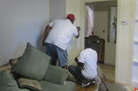 Two men working on a door in a house