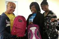 Three women holding backpacks